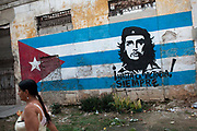 Woman walks past a Cuban flag with a picture of Che Guevara painted on it, with the words - victory always.