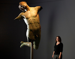 © Licensed to London News Pictures. 11/09/2012. LONDON, UK. A member of Royal Academy of the Arts staff looks at the 2000 year old 'Dancing Satyr' at the academy's latest exhibition entitled 'Bronze' in London today (11/09/12). The Satyr, discovered off the coast of Sicily in 1998 is considered one of the greatest of all classical bronzes, forms the signature piece for the exhibition that runs from 15 September to 9 December 2012. Photo credit: Matt Cetti-Roberts/LNP