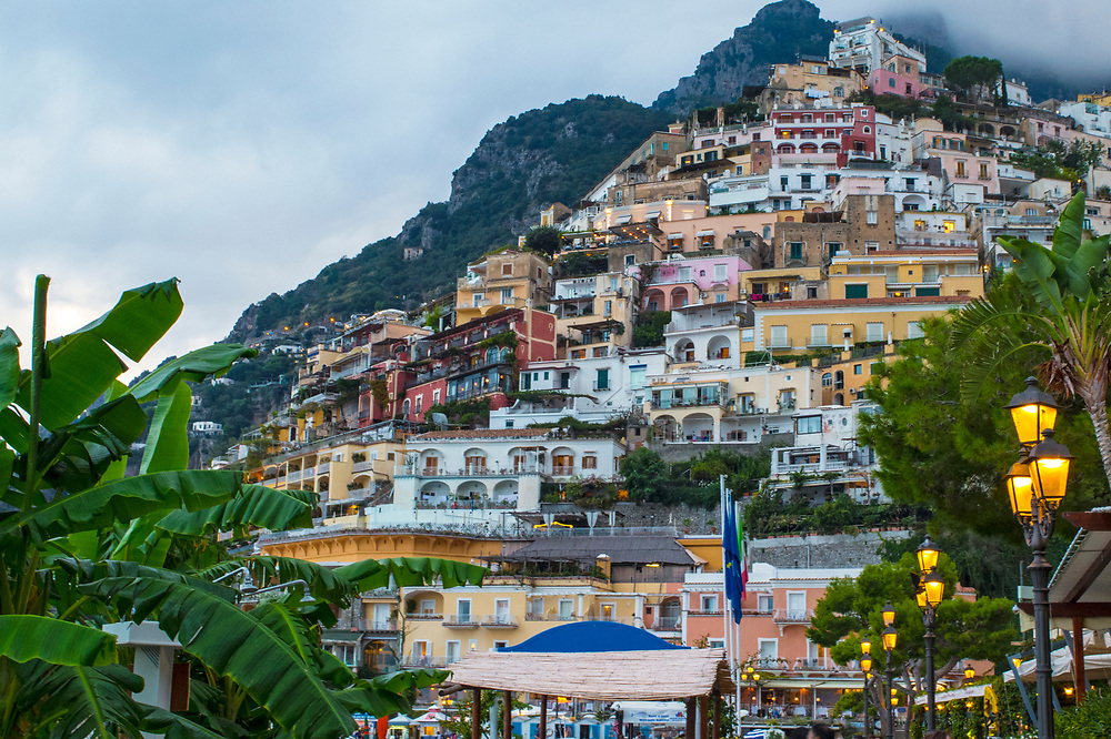 Colorful buildings on the hillside with palm trees and streetlights at dusk in Positano, Italy
