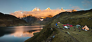 Sunrise illuminates the Cordillera Huayhuash above Carhuacocha lake campground (13,600 feet) in the Andes Mountains, Peru, South America. Peaks from left to right are: Siula Grande, Yerupaja Grande (6635 m or 21,770 ft, highest point in the Amazon watershed), Yerupaja Chico, and Mount Jirishanca (Icy Beak of the Hummingbird). Day 3 of 9 days trekking around the Cordillera Huayhuash. This panorama was stitched from 7 overlapping photos.