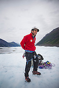St. Elias Alpine Guides tour guide Dan Hernandez prepares climbing gear for clients on an ice climbing day trip to the Root Glacier in Wrangell-St. Elias National Park, Alaska.