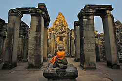 Sunset light refelcted off tip of Bayon Temple, with Buddha image in foreground courtyard covered with orange cloth
