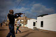 A rebel army volunteer shoots up a buildng run by Qadaffi in a town near Ras Lanuf  on March 3, 2011.