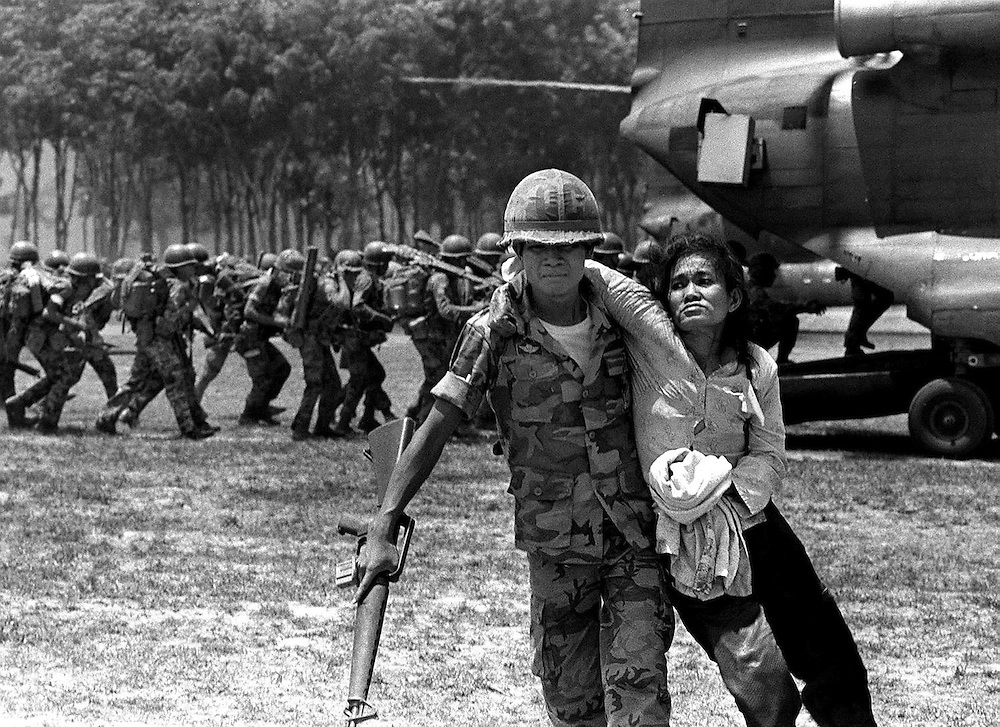 An exhausted woman is helped by a South Vietnamese soldier after the evacuation of Xuan Loc, Vietnam. 1975. Photograph by terry Fincher
