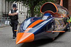 © licensed to London News Pictures. London, UK 24/06/2013. A police officer on Downing Street looking a replica of 13-metre long jet-and-rocket propelled Super Sonic Car car aims to beat the current land speed record of 763mph in 2014 and also to be the first land vehicle to exceed 1,000mph by 2015. Prime Minister is to announce a new apprenticeship initiative to create 100,000 Engineering Technicians. Photo credit: Tolga Akmen/LNP