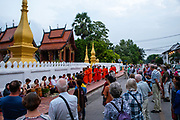 Monks and tourists particate in sai bat (morning alms giving), Wat Sensoukharam, along Sakkaline Road, Luang Prabang, Laos.