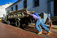 Construction workers try to start their truck by pushing it up the street. Casco Viejo, Panama.