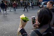 Before crossing the road, a woman takes a photo with her phone, of a bunch of flowers, on 25th January 2018, in London, England.