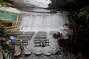 """Amazing Waterfall Restaurant<br /> <br /> Villa Escudero Resort is located in Quezon Province, Philippines, offering a vast hacienda filled with comfortable rooms, and a museum of curious things. Perhaps the most curious thing at the villa is the amazing Waterfalls Restaurant, where lunch is served against an impressive backdrop of thundering clear spring water. Grass fringed buffet stations and bamboo dining tables stand steadily in just inches of flowing river water from the sparkling falls, as it washes around the feet of diners enjoying delicious local dishes.<br /> <br /> The experience of dining as water is running over your feet would certainly create a memorable holiday moment, and possibly one of your most unusual experiences ever, as they boast this """"is a truly singular and memorable experience only Villa Escudero can offer.""""<br /> ©Villa Escudero Resort/Exclusivepix"""