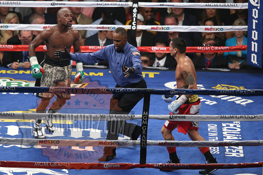 LAS VEGAS, NV - SEPTEMBER 13: (L-R) Floyd Mayweather Jr. yells at  Marcos Maidana during their WBC/WBA welterweight title fight at the MGM Grand Garden Arena on September 13, 2014 in Las Vegas, Nevada. (Photo by Alex Menendez/Getty Images) *** Local Caption *** Floyd Mayweather Jr; Marcos Maidana