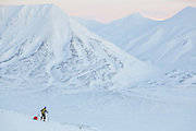 Mylène Jacquemart pulls a ski sled across Breinosa above Adventdalen, Svalbard at dawn.