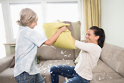 Woman pillow fighting with her son in living room, Bavaria, Germany
