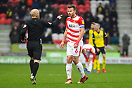 Andrew Butler of Doncaster Rovers (6) asks the referee Andy Woolmer a question, with a bemused look on his face during the EFL Sky Bet League 1 match between Doncaster Rovers and Scunthorpe United at the Keepmoat Stadium, Doncaster, England on 15 December 2018.