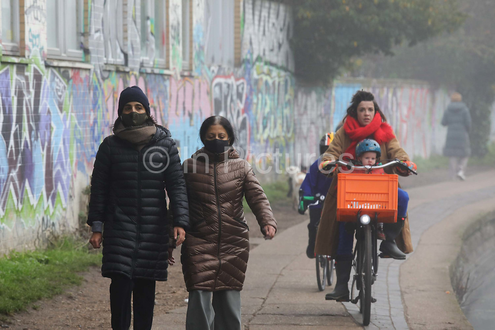 Two women wearing face masks walk along Regent's Canal on 27th of November 2020 in Hackney, London, United Kingdom. A woman with a child on her bike is about the pass. The canal is a popular place for runners, dog walkers and people in general and many use the tow path to commute. It is a misty and cold morning and the commuter rush hour by the canal is almost over.
