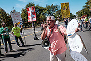 Pope Francis fan Esteban Burgoa, of Chicago, IL, tries to shout over the megaphone of  the Los Angeles chapter of Bible Believers following a short parade where Pope Francis was driven on the streets around the Ellipse, south of the White House in Washington, District of Columbia, U.S., on Wednesday, Sept. 23, 2015.