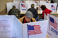 Jefferson County voter Dennis Frenzel cast his votes as other voters fill the booths during the general election Tuesday, Nov. 4, 2014 at the Arnold Recreation Center in Arnold. Among the high-profile races in the county is the race for Missouri State Senate in District 22, pitting Republican Paul Weiland against Democrat Jeff Roorda. Photo © copyright 2014 Sid Hastings.