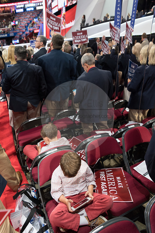 A young boy sits playing games on an iPad during the Republican National Convention July 20, 2016 in Cleveland, Ohio.