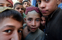 GERESHK,AFGHANISTAN - SEPT. 4: Children watch as a female Afghan inoculator administers the polio vaccination to the child of an Afghan woman  on the last day of a three-day nation wide immunisation campaign September 5, 2002 near Gereshk, Afghanistan.  The latest campaign targeted 5.9 million children under the age of five and teams of vaccinators went from village to village to ensure that all children in that age bracket were immunised. (Photo by Ami Vitale/Getty Images)