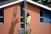 Nederland, Enschede, 3-10-2013Een glazenwasser lapt de ramen van een bedrijfspand, kantoor, kantoorpand.Foto: Flip Franssen/Hollandse Hoogte