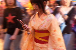 Young woman in kimono using mobile phone in Shinjuku nightlife district of Tokyo Japan