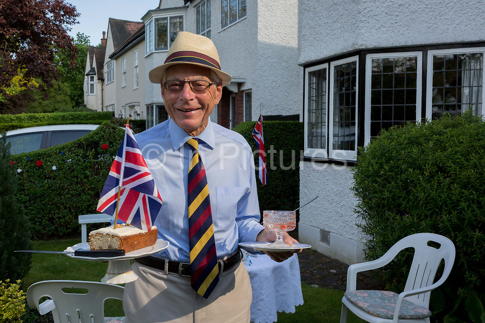 As the Coronavirus lockdown continues over the May Bank Holiday, the nation commemorates the 75th anniversary of VE Day Victory in Europe Day, the day that Germany officially surrendered in 1945 and in Dulwich, neighbours and residents emerge from their homes to party while still observing social distancing rules. A local resident clears away home-made cake back into his house after taking tea with distanced friends in his front garden, on 8th May 2020, in London, England.