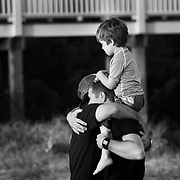 Buck Rowlee, Molly's Dad, hangs a friend while carrying Kieran (Molly's little brother) on his shoulders . The paddle-out in memory of Molly Rowlee, at Wrightsville Beach, NC. The event also helped support the Molly Fund  a non-profit dedicated to helping children with lymphoma and their families.