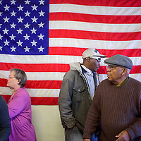 Immanuel Baptist Church pastor Garland Green, right, invites guests to take a seat where they will be served a turkey dinner during the church's 13th annual Thanksgiving event at the Community Outreach Center in Grants Saturday.