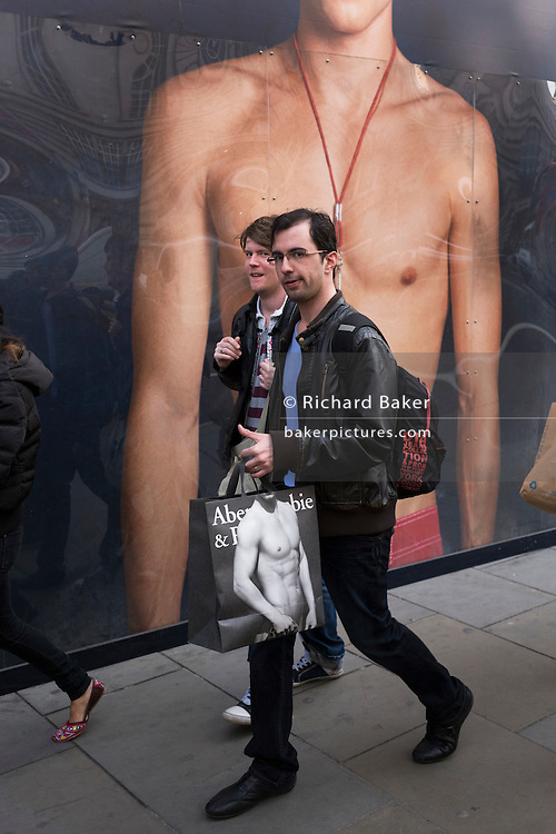Men walk past a giant ad mural of a bare-chested young male model, carrying Abercrombie shopping bags.