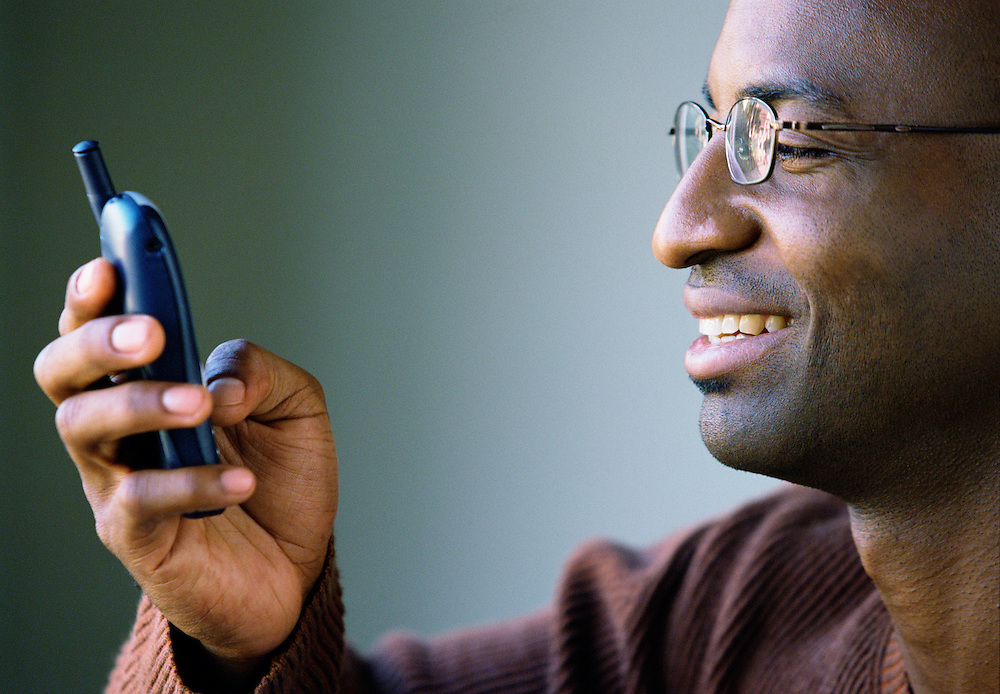 African American man text messaging on his cell phone.