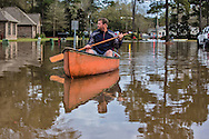 Covington Louisiana, March, 12, 2016,  Man paddles down a street in the Tallow Creek subdivision. 14 inches of rain fell in less than 24 hours, after three days of intermittent rain, causing flash floods. The Tchefuncte River  and Bogue Falaya River<br />  crested on Saturday morning but the flood event continued into the night for those in Tallow Creek.