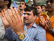 31 AUGUST 2014 - SARIKA, NAKHON NAYOK, THAILAND: Men pray during the Ganesh festival at Shri Utthayan Ganesha Temple in Sarika, Nakhon Nayok. Ganesh Chaturthi, also known as Vinayaka Chaturthi, is a Hindu festival dedicated to Lord Ganesh. It is a 10-day festival marking the birthday of Ganesh, who is widely worshiped for his auspicious beginnings. Ganesh is the patron of arts and sciences, the deity of intellect and wisdom -- identified by his elephant head. The holiday is celebrated for 10 days, in 2014, most Hindu temples will submerge their Ganesh shrines and deities on September 7. Wat Utthaya Ganesh in Nakhon Nayok province, is a Buddhist temple that venerates Ganesh, who is popular with Thai Buddhists. The temple draws both Buddhists and Hindus and celebrates the Ganesh holiday a week ahead of most other places.    PHOTO BY JACK KURTZ