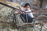 Young girl sits in a rusty cart in a barn