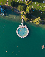 Aerial view of an outdoor public pool that looks like the search logo. a slide in the shape of the g of google and some swimmer in Zürich Switzerland