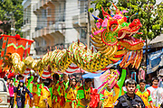 """05 JULY 2014 - BANGKOK, THAILAND:  Chinese style dragon dancers perform on a side street in Bangkok during a parade for vassa. Vassa, called """"phansa"""" in Thai, marks the beginning of the three months long Buddhist rains retreat when monks and novices stay in the temple for periods of intense meditation. Vassa officially starts July 11 but temples across Bangkok are holding events to mark the holiday all week.   PHOTO BY JACK KURTZ"""