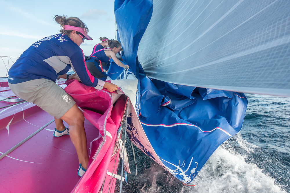 January, 2015. Leg 3 onboard Team SCA. Sally Barkow helps pull the J1 sail on board after the Team changes sails.