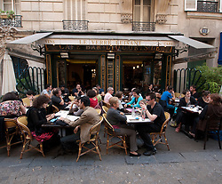 Typical busy pavement restaurant in the Marais district of Paris France
