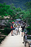 A small group of cyclists standing on a bridge that crosses the Yulong River near Yangshuo.