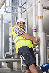 Male engineer pulling lever in Geothermal Power Station, Bavaria, Germany