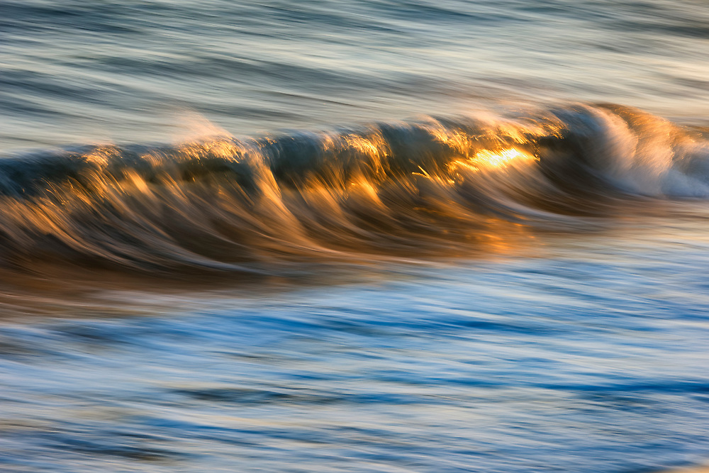 A long exposure elongates the waves that touch the shore of Port Hueneme Beach at sunset.