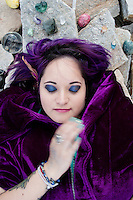 Sensitive magical woman in a purple cloak with a crystal crown chakra altar for sky gazing meditation in sacred place.