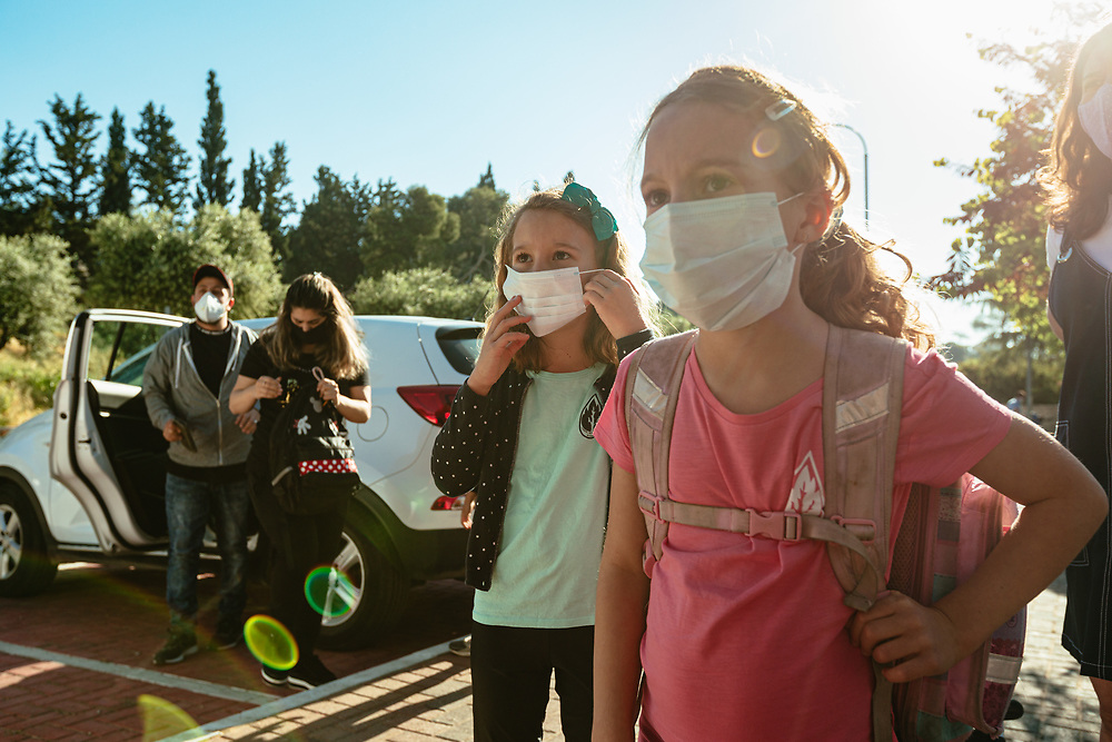 Twin girls Alma (3rd R) and Clil (2nd R), and their mother Anna Michel (R), wearing protective face masks, are seen as they await their turn to enter the elementary school where the girls study, in Jerusalem, Israel, on May 3, 2020.