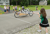 Leia Donahue waves the checkered flag as Lauren Donahue crosses the finish line during the 2nd annual Franklin Elks Soap Box Derby on Saturday.  (Karen Bobotas/for the Laconia Daily Sun)