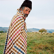 Portrait of Mihai Vlad, a shepherd in Soars village, Saxon Transylvania, Romania. His shepherds cloak, a handwoven checked woollen blanket is particular to this area. Whereas in most countries sheep are reared for wool and meat, in Romania these are seen as by-products and the real purpose of the flock is to produce branza or cheese.