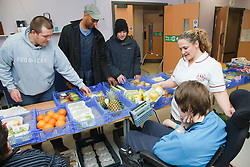 Young disabled client who has Cerebral Palsy buying fresh vegetables form a stall run by people with learning disabilities at a resource for people with physical and sensory impairment.