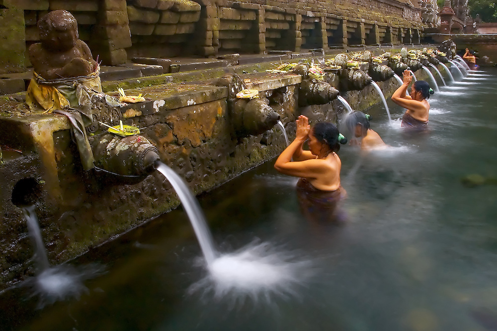 Multiple exposure photo of a Balinese lady praying at the fountains of Tirta Empul Temple, Tampaksiring, Bali