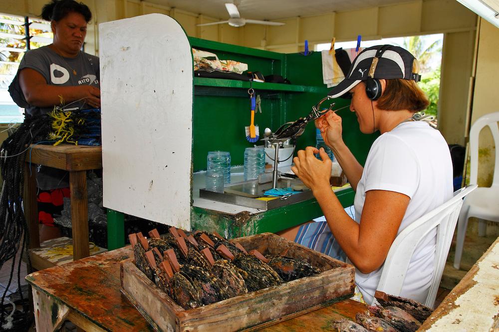Trabajador de una granja de perlas manioulando una ostra, Rangiroa, Archipiélago Tuamotu, Polinesia Francesa