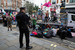 London, UK. 23rd August, 2021. Environmental activists from Extinction Rebellion assemble around a vehicle used with lock-ons to block a road in the Covent Garden area during the first day of Impossible Rebellion protests. Extinction Rebellion are calling on the UK government to cease all new fossil fuel investment with immediate effect. Credit: Mark Kerrison/Alamy Live News