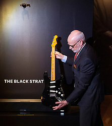 David Gilmour Guitar Collection<br /> Press view<br /> <br /> The Black Strat held by Kerry Keane Christie's musical instrument specialist <br /> Fender electric instrument company <br /> A solid body. electric guitar Stratocaster <br /> Estimated $100,000 to $150,000<br /> <br /> The personal guitar collection of rock'n'roll legend David Gilmour, guitarist, singer and songwriter of Pink Floyd is unveiled at Christies, London, Great Britain <br /> 27th March 2019<br /> <br /> For the very first time, Christie's will unveil the much-anticipated preview of the personal guitar collection of rock'n'roll legend David Gilmour, guitarist, singer and songwriter of Pink Floyd, to media on Wednesday 27 March at 9.30am. The first stop for the pre-sale touring exhibition, the view will provide a once in a lifetime opportunity to see the 120+ guitar highlights being sold,<br /> with proceeds to benefit charity.<br />  <br /> The exhibition will be on view to the public from 27 to 31 March 2019. Entry will be free, with timed-tickets.<br /> <br /> Photograph by Elliott Franks