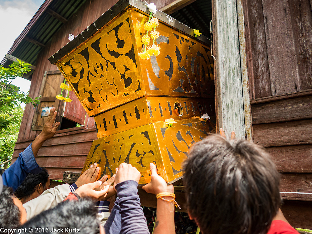 20 JUNE 2016 - DON KHONE, CHAMPASAK, LAOS:  Men lift the coffin of a friend out of his home during his funeral in Don Khone village on Don Khone Island. Don Khone Island, one of the larger islands in the 4,000 Islands chain on the Mekong River in southern Laos. The island has become a backpacker hot spot, there are lots of guest houses and small restaurants on the north end of the island.    PHOTO BY JACK KURTZ
