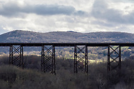 Cornwall, New York - Sunlight and clouds in a view of the Moodna Viaduct railroad trestle and Schunnemunk Mountain on Apri. 15, 2019.